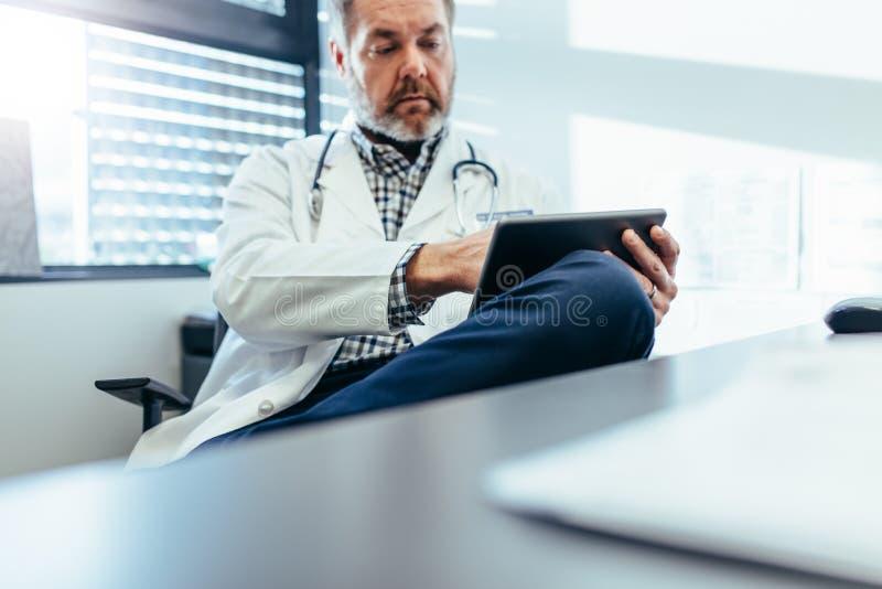 Ιατρός που χρησιμοποιεί το PC ταμπλετών στην κλινική του στοκ φωτογραφίες