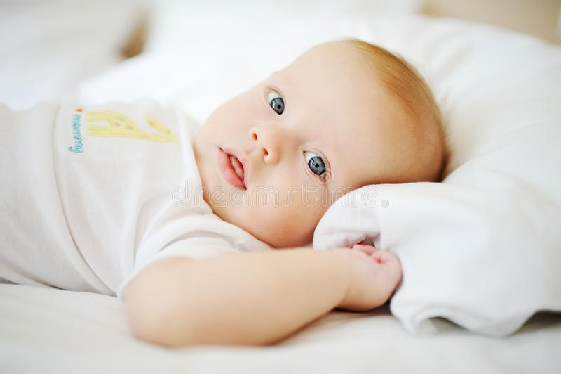 διαφήμισης μεγάλο πορτρέτο ματιών επιλογής μωρών μπλε Ένα παιδί που στηρίζεται σε ένα κρεβάτι στοκ φωτογραφία