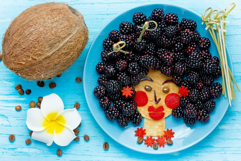 Ιδέα τροφίμων διασκέδασης για τα παιδιά - εδώδιμο της Χαβάης πρόσωπο κοριτσιών από την τηγανίτα και το βατόμουρο, τέχνη τροφίμων στοκ εικόνα