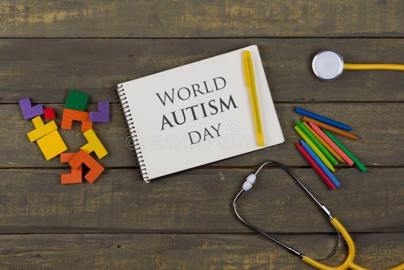 Ιδέα ψυχικής υγείας - κείμενο Παγκόσμια Ημέρα Αυτισμού, σημειωματάριο, κίτρινο στηθοσκόπιο, πολύχρωμα ξύλινα παζλ, κραγιόνια στοκ εικόνα με δικαίωμα ελεύθερης χρήσης