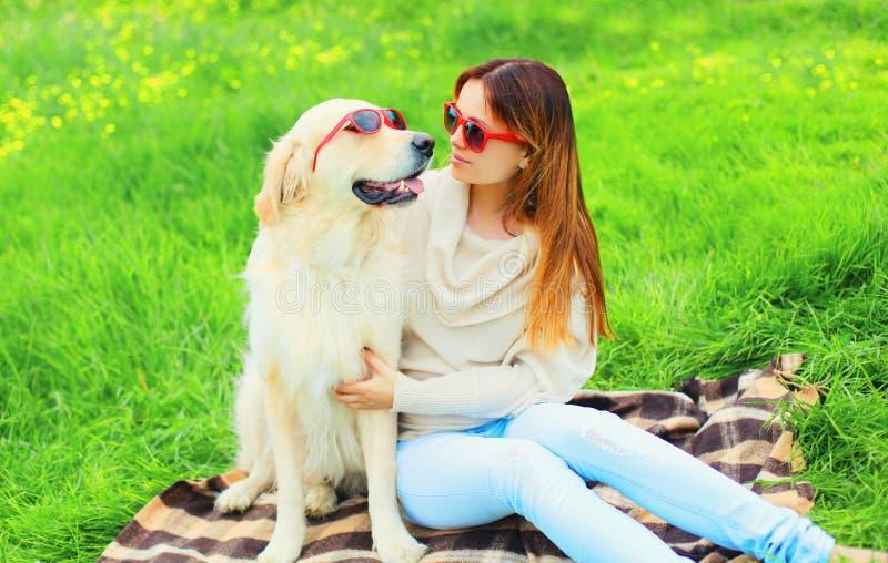 ιδιοκτήτης γυναικών και χρυσό Retriever σκυλί στα γυαλιά ηλίου μαζί στη χλόη το καλοκαίρι στοκ φωτογραφίες