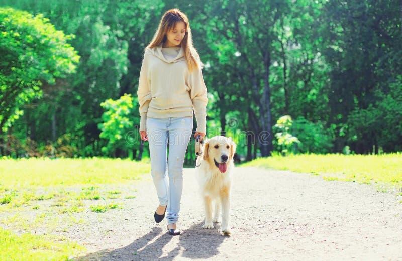 Ιδιοκτήτης γυναικών που περπατά με το χρυσό Retriever της σκυλί στο λουρί το καλοκαίρι στοκ φωτογραφίες