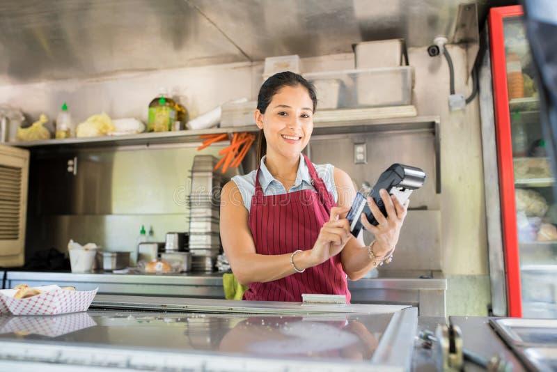 Ιδιοκτήτης φορτηγών τροφίμων με το τερματικό πιστωτικών καρτών στοκ εικόνες