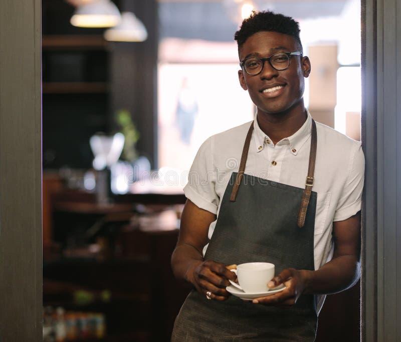 Ιδιοκτήτης Café στη καφετερία του που κρατά ένα φλυτζάνι καφέ στοκ εικόνες