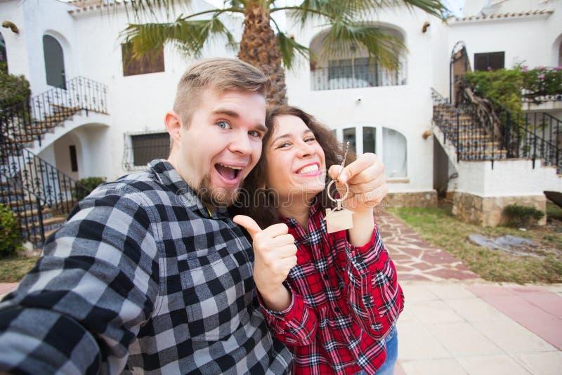 Ιδιοκτησία, ακίνητη περιουσία και έννοια διαμερισμάτων - ευτυχής αστεία νέα παρουσίαση ζευγών κλειδιά του καινούργιου σπιτιού του στοκ εικόνες
