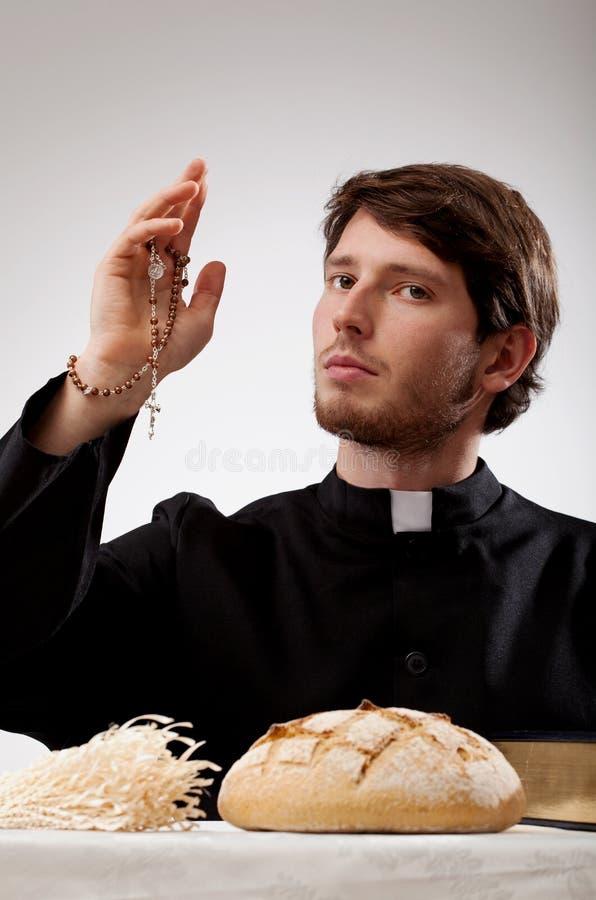 Ιερέας με rosary, το ψωμί και τη Βίβλο στοκ εικόνες με δικαίωμα ελεύθερης χρήσης