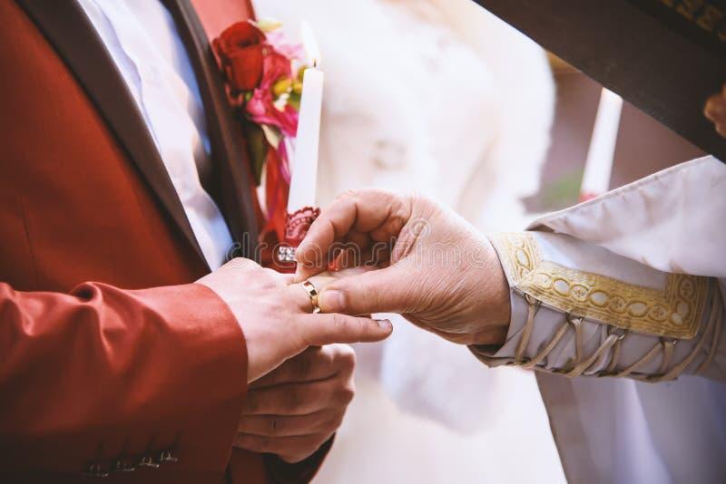 Ιερέας που βάζει το γαμήλιο δαχτυλίδι στο δάχτυλο νεόνυμφων, όρκος γάμου, χριστιανικές παραδόσεις στοκ εικόνες με δικαίωμα ελεύθερης χρήσης