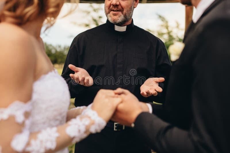 Ιερέας που δίνει τις ευλογίες στη νύφη και στο νεόνυμφο στοκ εικόνες
