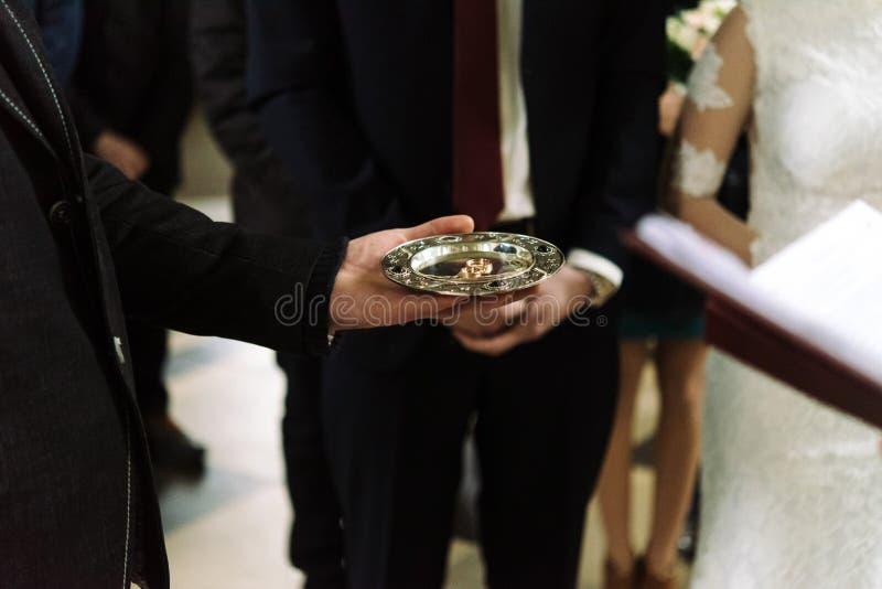 Ιερέας που ευλογεί τα γαμήλια δαχτυλίδια πολυτέλειας στην παλαιά εκκλησία στοκ φωτογραφία