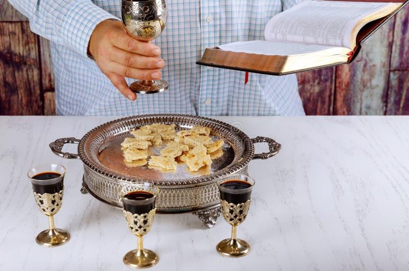 Ιερή κοινωνία στον ξύλινο πίνακα στο φλυτζάνι εκκλησιών του γυαλιού με το κόκκινο κρασί, ψωμί, προσευχή για το κρασί στοκ εικόνες