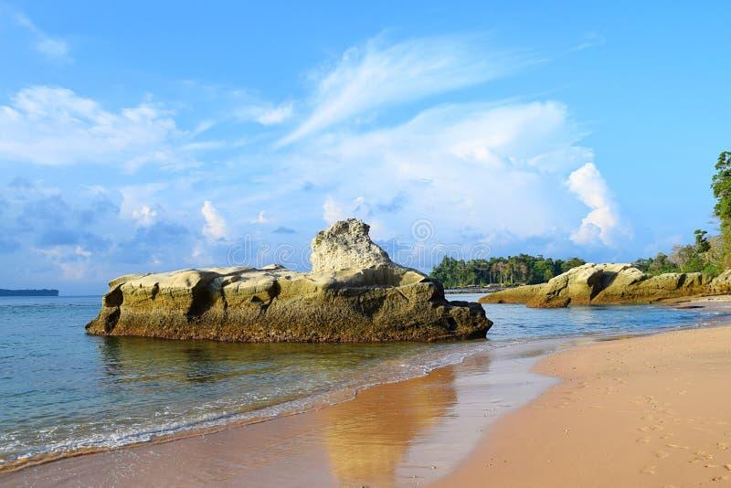 Ιζηματώδης πέτρινος βράχος ασβέστη στο ήρεμο θαλάσσιο νερό, μπλε ουρανός με τα άσπρα σύννεφα, και αμμώδης παραλία - τοπίο σε Sita στοκ φωτογραφία με δικαίωμα ελεύθερης χρήσης