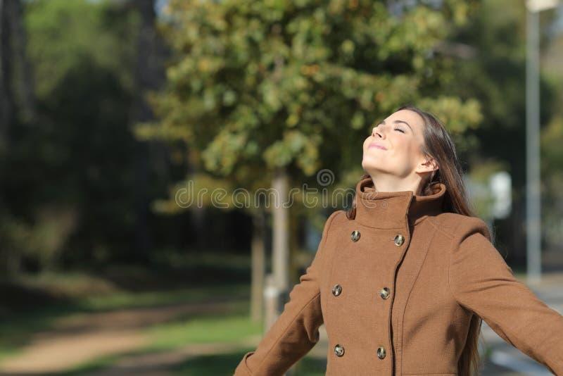 Ικανοποιημένη γυναίκα που αναπνέει καθαρό αέρα σε πάρκο στοκ φωτογραφία με δικαίωμα ελεύθερης χρήσης