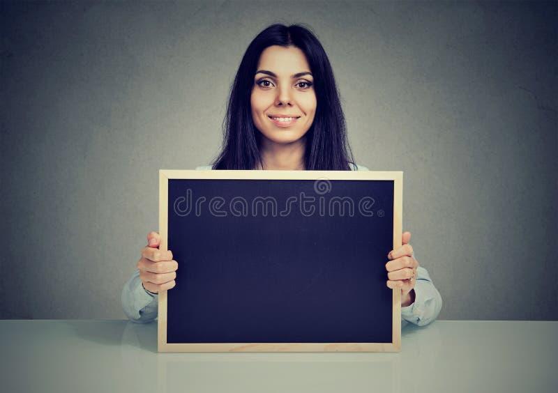 Ικανοποιημένη γυναίκα που παρουσιάζει κενό πίνακα στοκ φωτογραφία