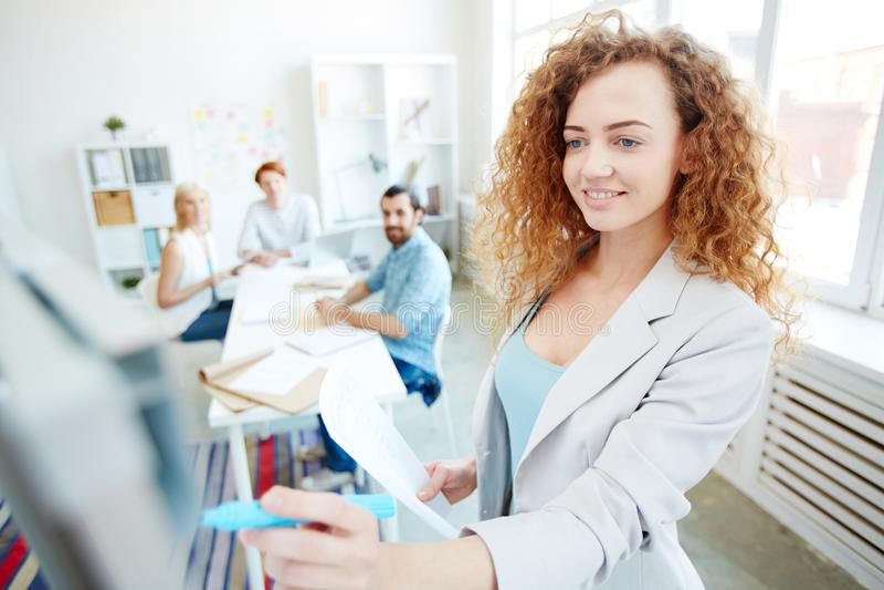 Ικανοποιημένη επιχειρηματίας που εξηγεί τις πληροφορίες στους συναδέλφους στοκ εικόνες