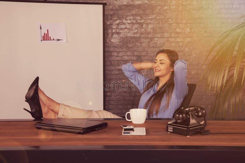 Ικανοποιημένη επιχειρηματίας, που κάθεται στο γραφείο και να ονειρευτεί το abou στοκ εικόνες
