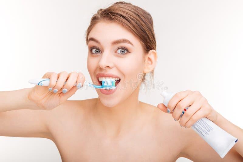 Ικανοποιημένη καλή γυναίκα που βουρτσίζει τα δόντια της με την οδοντόπαστα και την οδοντόβουρτσα στοκ εικόνες