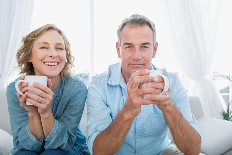Ικανοποιημένη μέση ηλικίας συνεδρίαση ζευγών στον καναπέ που έχει τον καφέ στοκ εικόνες με δικαίωμα ελεύθερης χρήσης