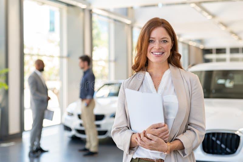 Ικανοποιημένη πωλήτρια στη εμπορία αυτοκινήτων στοκ εικόνα με δικαίωμα ελεύθερης χρήσης