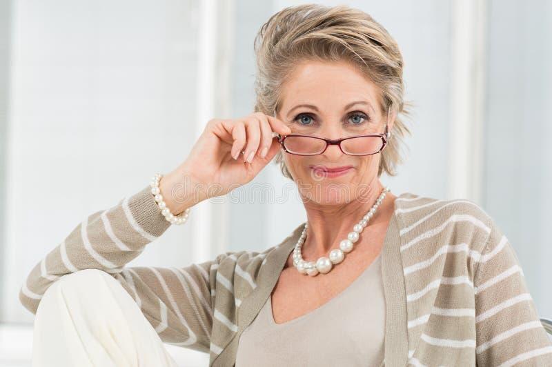Ικανοποιημένη ώριμη γυναίκα που φορά Eyeglass στοκ φωτογραφίες με δικαίωμα ελεύθερης χρήσης