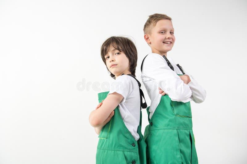 Ικανοποιημένοι τεχνικοί που φορούν τις πράσινες φόρμες στοκ εικόνες