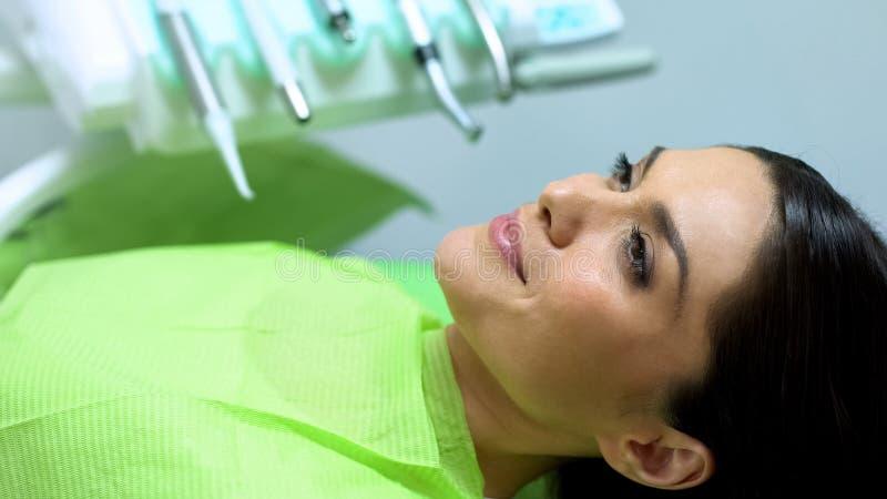 Ικανοποιημένος ασθενής που έχει το υπόλοιπο μετά από τη διαδικασία οδοντιατρικής, επαγγελματική υπηρεσία στοκ εικόνα