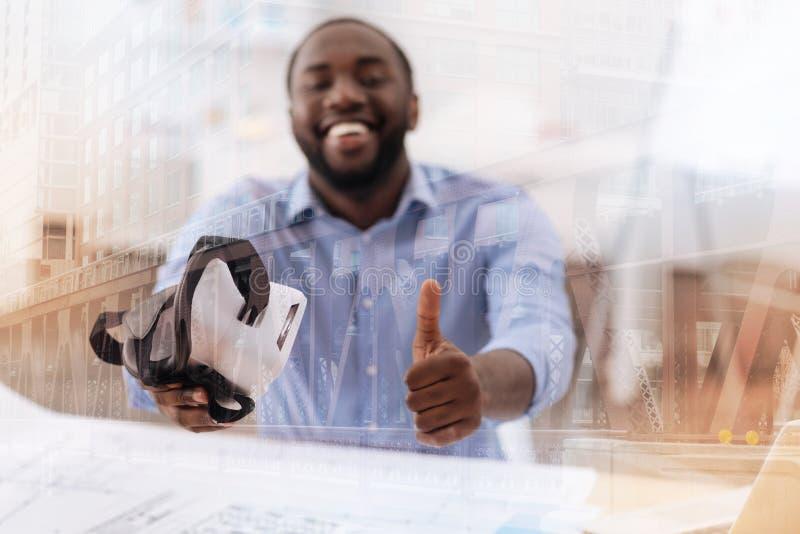 Ικανοποιημένος αφροαμερικάνος που κρατά την εικονική μάσκα στο χέρι του στοκ εικόνες