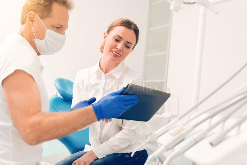 Ικανοποιημένος θηλυκός ασθενής που εξετάζει τον υπολογιστή ταμπλετών στην οδοντική κλινική στοκ φωτογραφία με δικαίωμα ελεύθερης χρήσης