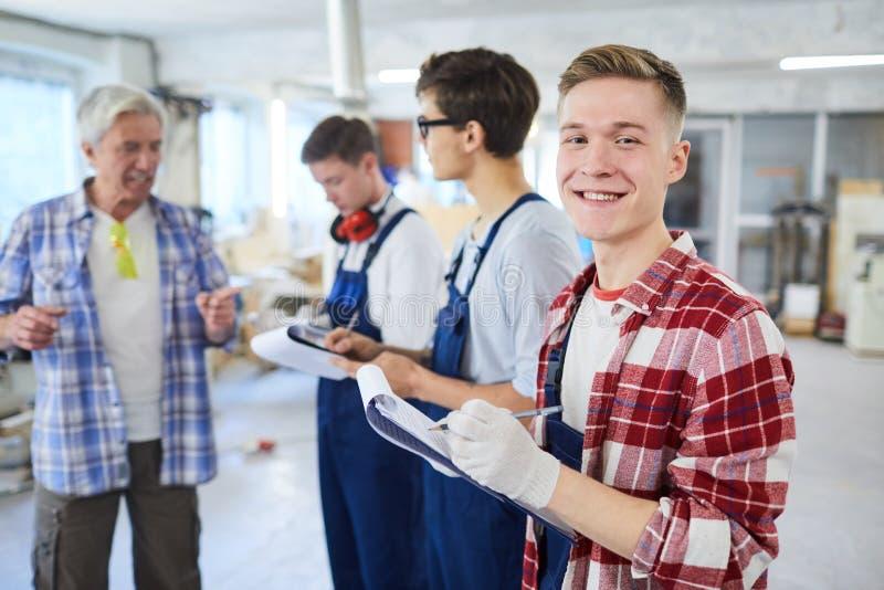 Ικανοποιημένος νέος εργαζόμενος ξυλουργικής που κάνει τις σημειώσεις στην περιοχή αποκομμάτων στοκ εικόνα