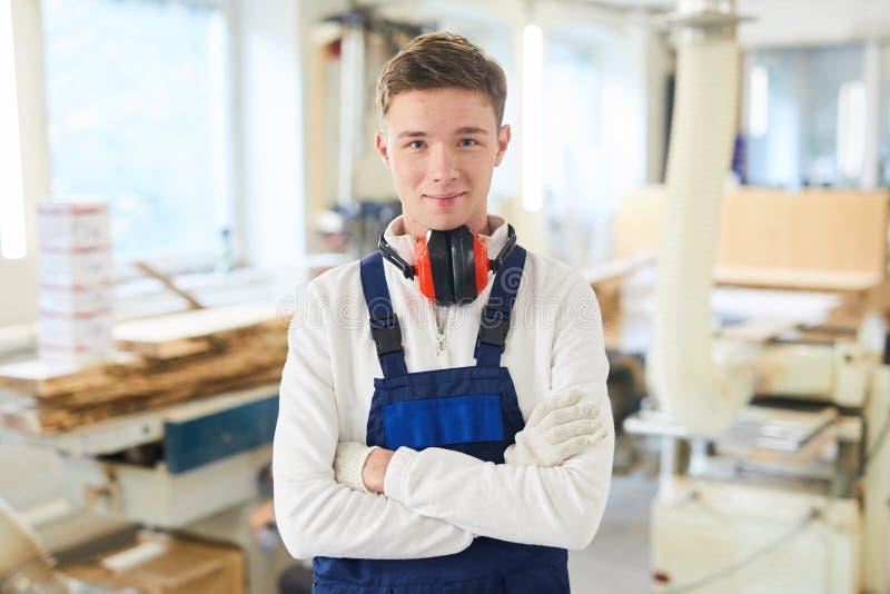 Ικανοποιημένος νέος ξυλουργός στο εργαστήριο στοκ εικόνες