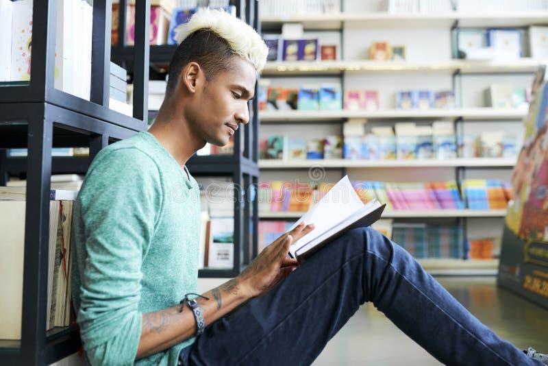 Ικανοποιημένος φοιτητής πανεπιστημίου που παίρνει τη νέα γνώση στη βιβλιοθήκη στοκ φωτογραφία