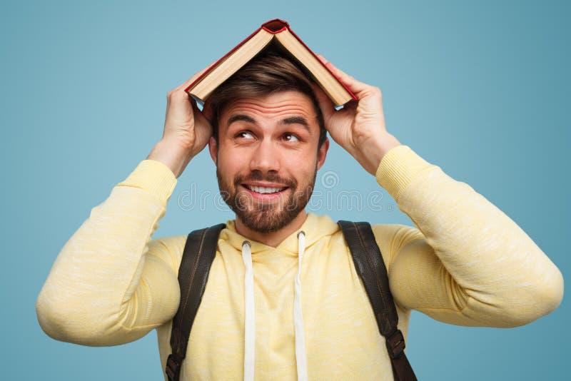 Ικανοποιημένο άτομο που καλύπτει το κεφάλι με το βιβλίο στοκ εικόνα