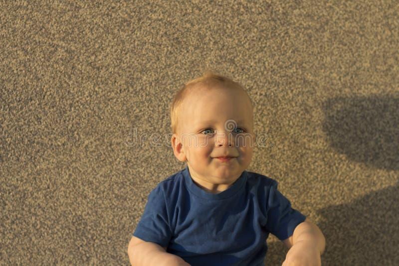 Ικανοποιημένο αγοράκι στα πλαίσια ενός συμπαγούς τοίχου Παιδί νηπίων με τις ασυνήθιστες σκιές στο πρόσωπό του στοκ φωτογραφίες