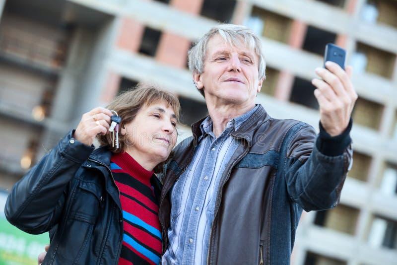 Ικανοποιημένο ανώτερο ζεύγος με τα κλειδιά σπιτιών που κάνουν selfie από κοινού στοκ εικόνες