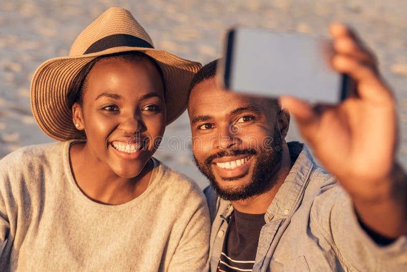 Ικανοποιημένο νέο αφρικανικό ζεύγος που παίρνει selfies μαζί στην παραλία στοκ εικόνες με δικαίωμα ελεύθερης χρήσης