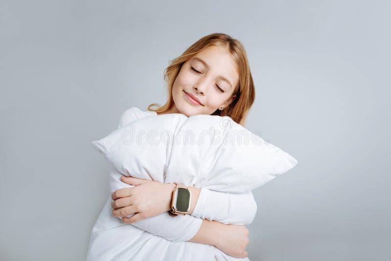 Ικανοποιημένο χαριτωμένο κορίτσι που αγκαλιάζει το μαξιλάρι στοκ φωτογραφία