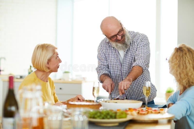 Ικανοποιημένο ώριμο τέμνον κρέας ατόμων για τους φιλοξενουμένους στοκ εικόνες