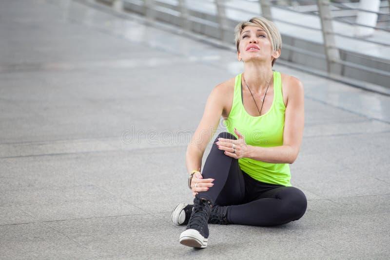 ικανότητας νέο ατύχημα ποδιών τραυματισμών γυναικών τρέχοντας του workout που ασκεί στην οδό στην αστική πόλη συνεδρίαση κοριτσιώ στοκ φωτογραφία