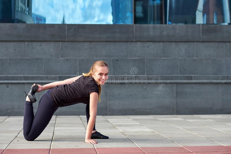 Ικανότητα, αθλητισμός, έννοια κατάρτισης, γυμναστικής και τρόπου ζωής - νέα γυναίκα τεντώματος με τα ακουστικά στη γυμναστική στοκ φωτογραφία με δικαίωμα ελεύθερης χρήσης