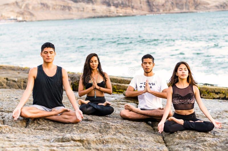 Ικανότητα, αθλητισμός, γιόγκα και υγιής έννοια τρόπου ζωής - ομάδων ανθρώπων στο λωτό θέτει στοκ φωτογραφία
