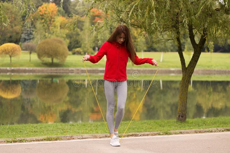Ικανότητα, αθλητισμός, κατάρτιση, πάρκο και έννοια τρόπου ζωής - χαμογελώντας λευκή γυναίκα που ασκεί με το άλμα-σχοινί υπαίθρια στοκ φωτογραφίες