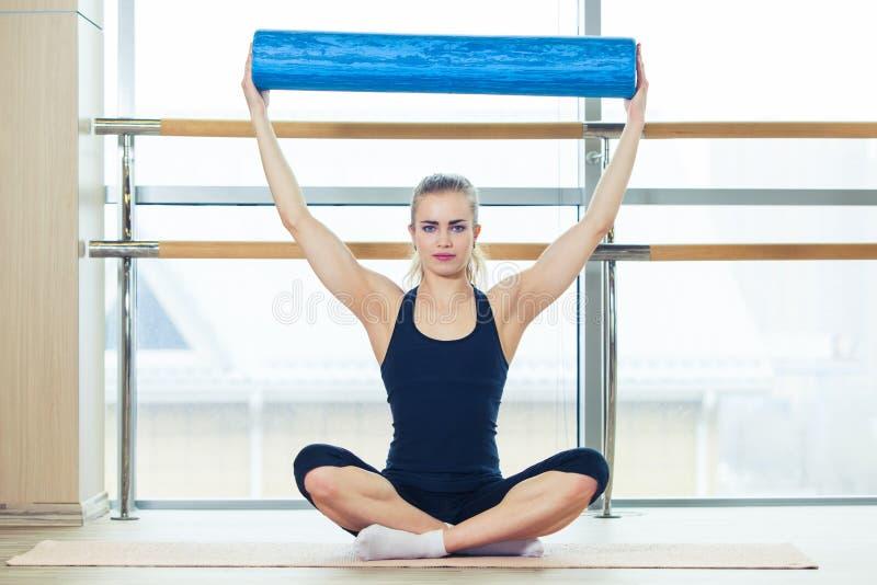 Ικανότητα, αθλητισμός, έννοια κατάρτισης και τρόπου ζωής - γυναίκα που κάνει pilates στο πάτωμα με τον κύλινδρο αφρού στοκ φωτογραφία