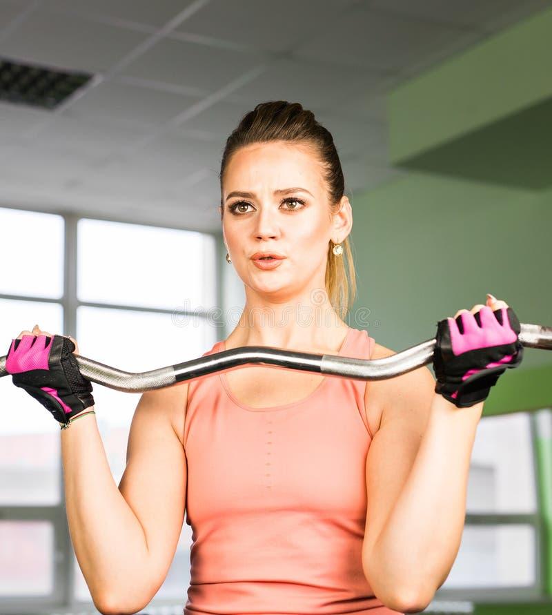 Ικανότητα, αθλητισμός, έννοια κατάρτισης και τρόπου ζωής - ευτυχής γυναίκα με τους μυς κάμψης barbell στη γυμναστική στοκ εικόνα