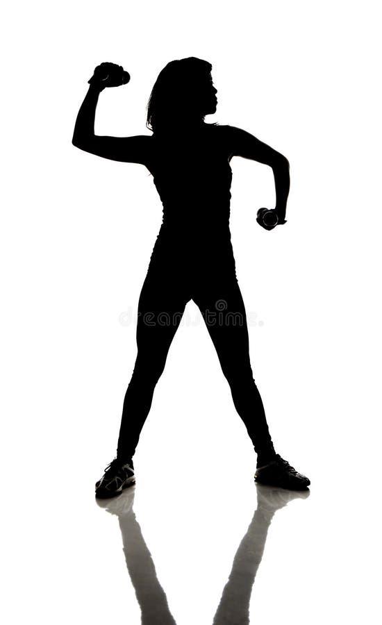 Ικανότητα: Σκιαγραφία της athletically κατάλληλης γυναίκας που κάνει τις μπούκλες με τους αλτήρες στοκ εικόνες με δικαίωμα ελεύθερης χρήσης