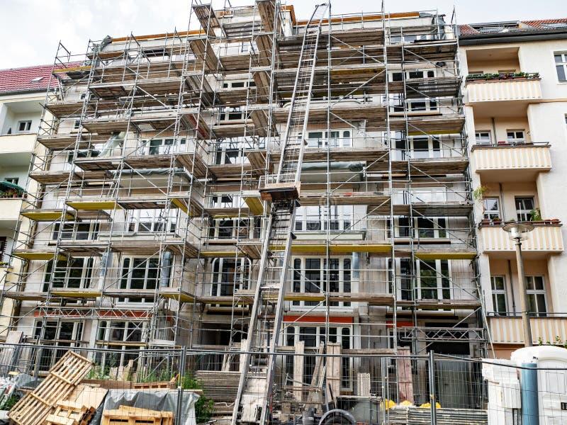 Ικρίωμα που περιβάλλει τη νέα κατασκευή ολοκλήρωσης οικοδόμησης στοκ εικόνα με δικαίωμα ελεύθερης χρήσης