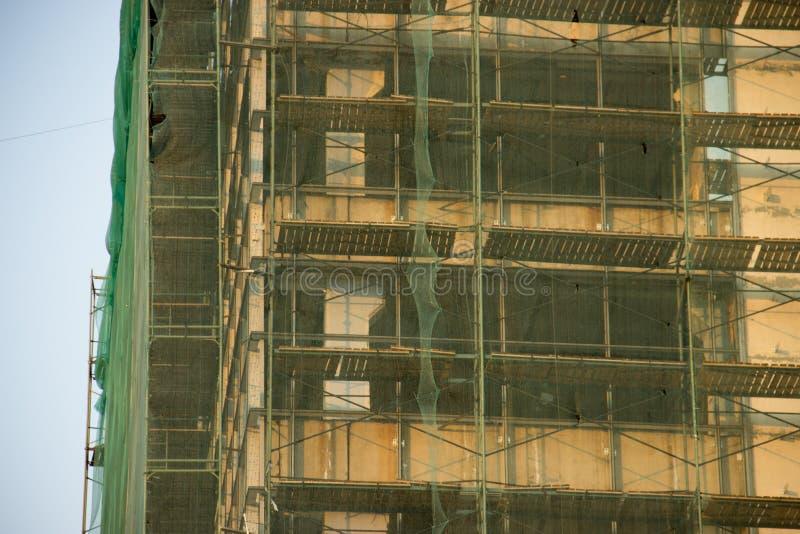 Ικρίωμα σε ένα παλαιό σπίτι για την ανακαίνιση Μπεζ, πράσινο και μπλε υπόβαθρο Ocher Αναδημιουργία των κτηρίων και των δομών Elem στοκ εικόνα