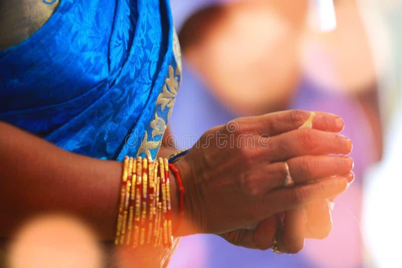Ινδική γαμήλια λειτουργία, χέρι γυναικών κινηματογραφήσεων σε πρώτο πλάνο με τα λουλούδια και τα φω'τα στοκ φωτογραφίες
