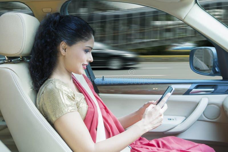 Ινδική γυναίκα που χρησιμοποιεί ένα κινητό τηλέφωνο στο αυτοκίνητο στοκ φωτογραφίες