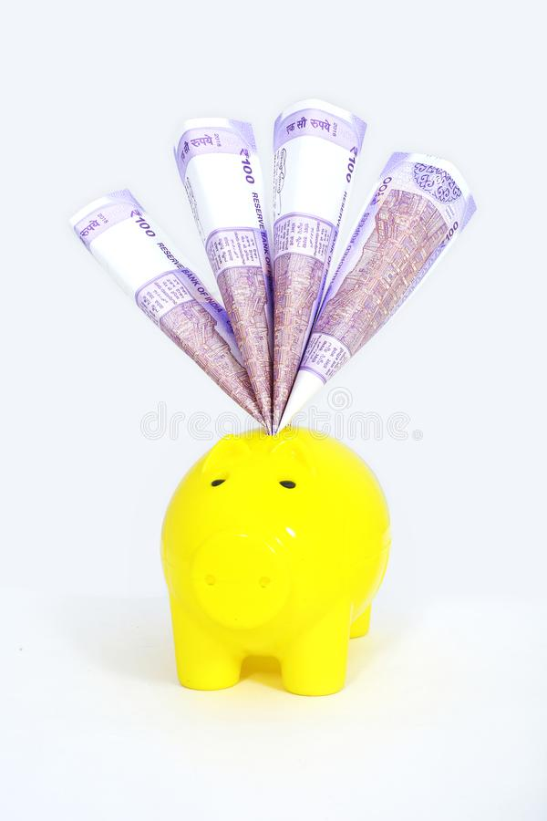Ινδική σημείωση νομίσματος 100 ρουπίων στη piggy τράπεζα στοκ φωτογραφία