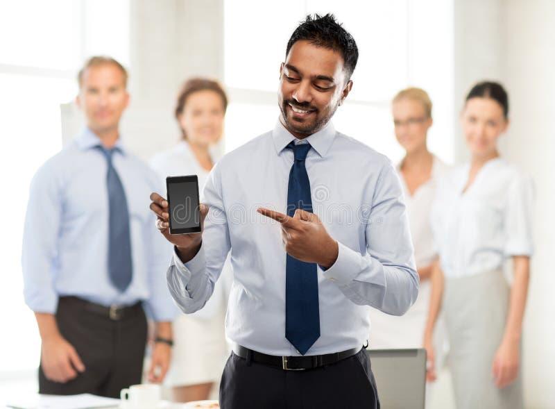 Ινδικός επιχειρηματίας που παρουσιάζει smartphone στο γραφείο στοκ φωτογραφία