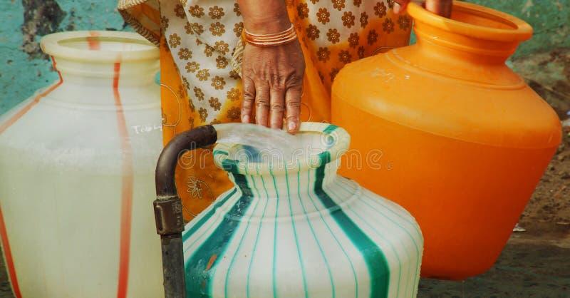 Ινδικός σωλήνας στάσεων νερού που γεμίζει ένα πλαστικό δοχείο νερού η γυναίκα φέρνει το δοχείο νερού στοκ φωτογραφία με δικαίωμα ελεύθερης χρήσης